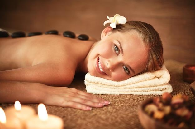 Szczęśliwa kobieta z gorącymi kamieniami w spa