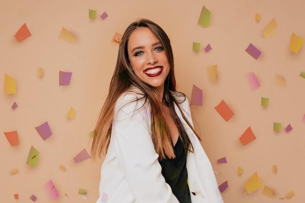 Szczęśliwa kobieta z jasnym makijażem, taniec pod błyszczącym konfetti i dobrą zabawę. ładna dziewczyna kaukaski w stroju imprezowym pozuje podczas sesji zdjęciowej