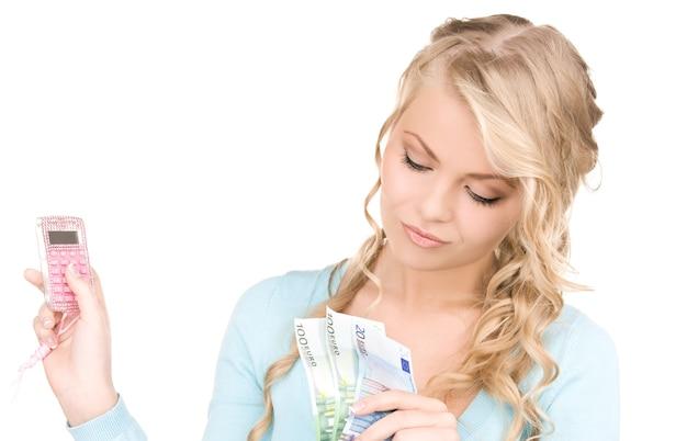 Szczęśliwa kobieta z kalkulatorem i pieniędzmi na białym