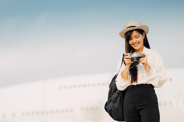 Szczęśliwa kobieta z kamery czekaniem dla podróży samolotem.