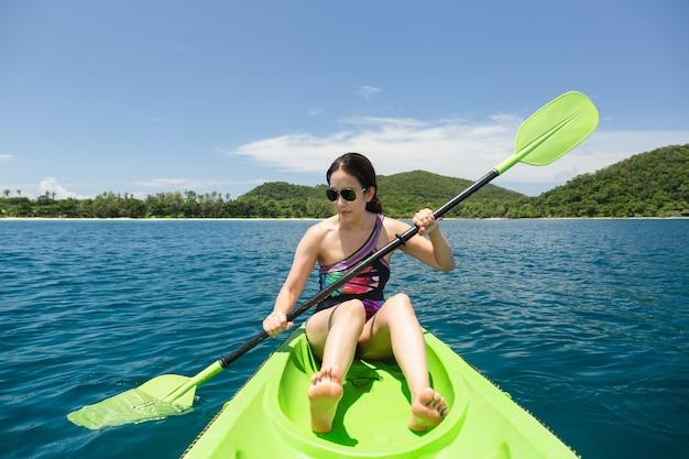 Szczęśliwa kobieta z kamizelką ratunkową kajakiem w tropikalnej wyspie oceanu na wakacjach.