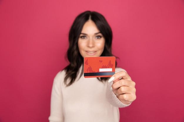 Szczęśliwa kobieta z kartą kredytową na białym tle w różowym studio.