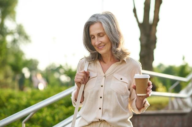 Szczęśliwa kobieta z kawą spacerująca w parku