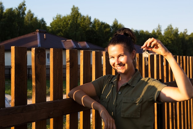 Szczęśliwa kobieta z kluczami do domu w dłoni w pobliżu drewnianego ogrodzenia domu