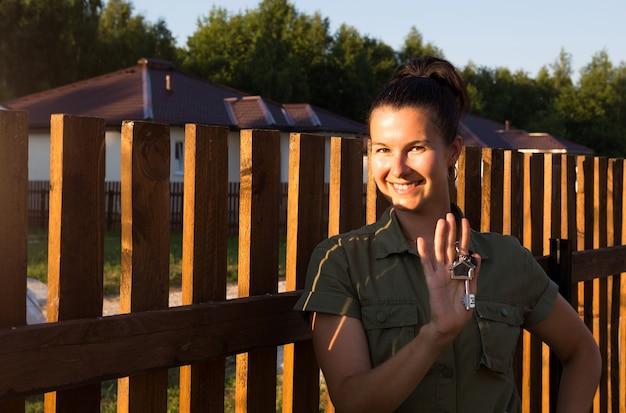 Szczęśliwa kobieta z kluczami do domu w dłoni w pobliżu drewnianego ogrodzenia swojego domu w wiejskiej wiosce