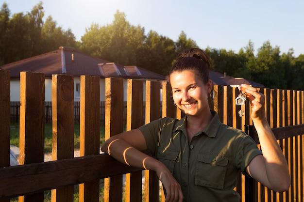 Szczęśliwa kobieta z kluczami do domu w ręku w pobliżu drewnianego ogrodzenia jej domu w wiosce domków. właściciel nieruchomości, agent, pośrednik w obrocie nieruchomościami. przeprowadzka, kupno mieszkania. kredyt hipoteczny i czynsz. skopiuj miejsce