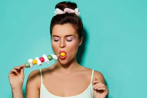 Szczęśliwa kobieta z kolorowy makijaż i słodkie cukierki na szpikulec