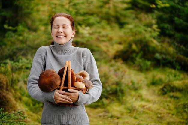 Szczęśliwa kobieta z koszem grzybów w leśnej koncepcji turystyki pieszej i ekoturystyki