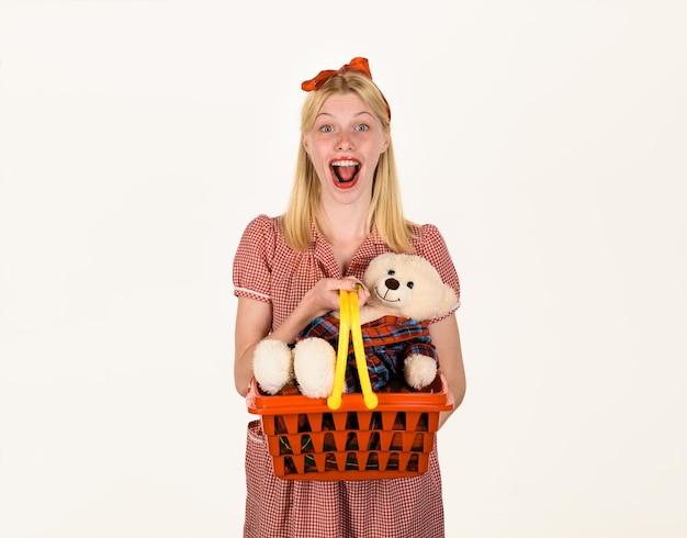 Szczęśliwa kobieta z koszem na zakupy uśmiechnięta dziewczyna z misiem w supermarkecie rabat sprzedaży