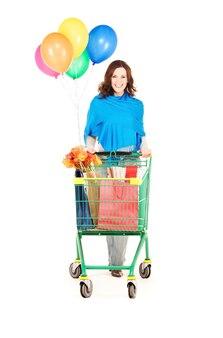 Szczęśliwa kobieta z koszykiem i balonami nad białą ścianą