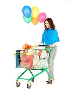 Szczęśliwa kobieta z koszykiem i balonami nad białymi