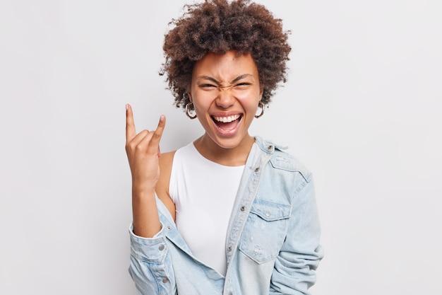 Szczęśliwa kobieta z kręconymi włosami pokazuje gest rock and rolla heavy metalowy znak cieszy się ulubioną muzyką na imprezie ma zabawy mruży oczy twarz woła z radości nosi dżinsową koszulę na białym tle nad białą ścianą