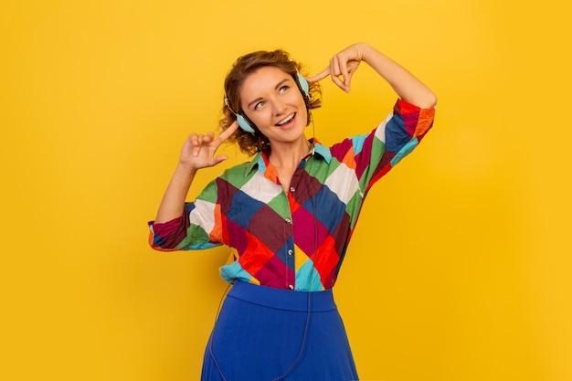 Szczęśliwa kobieta z krótką fryzurą słuchająca muzyki przez słuchawki i bawiąca się na żółtej ścianie