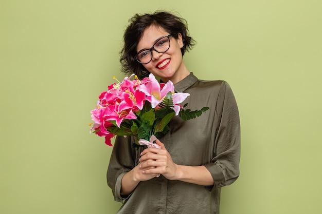 Szczęśliwa kobieta z krótkimi włosami trzyma bukiet kwiatów patrząc na kamerę uśmiechając się radośnie świętując międzynarodowy dzień kobiet 8 marca stojąc na zielonym tle