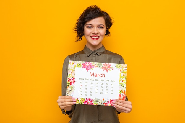 Szczęśliwa kobieta z krótkimi włosami trzyma papierowy kalendarz miesiąca marca patrząc na kamerę uśmiechając się radośnie świętując międzynarodowy dzień kobiet 8 marca stojąc na pomarańczowym tle