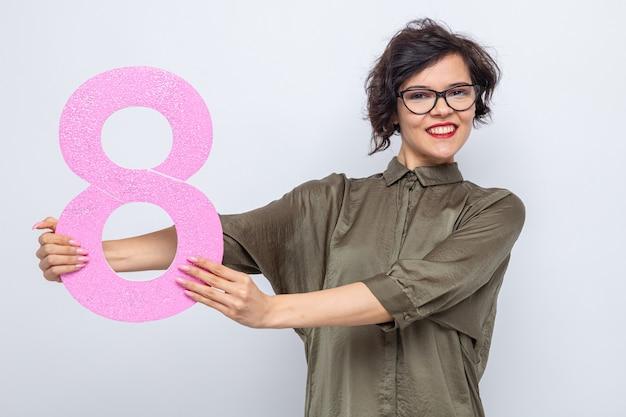 Szczęśliwa kobieta z krótkimi włosami trzymająca cyfrę osiem z tektury patrząca w kamerę uśmiechnięta radośnie świętująca międzynarodowy dzień kobiet 8 marca stojąca na białym tle