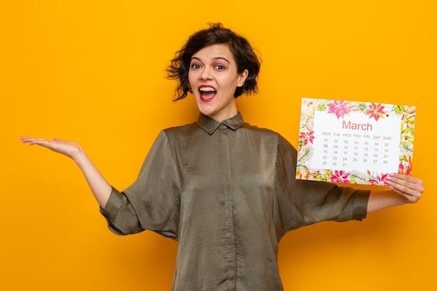 Szczęśliwa kobieta z krótkimi włosami trzymająca papierowy kalendarz miesiąca marzec uśmiechając się radośnie prezentując ramieniem dłoni świętujący międzynarodowy dzień kobiet 8 marca stojąc na pomarańczowym tle