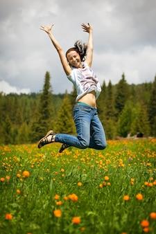 Szczęśliwa kobieta z kwiatami na letniej łące