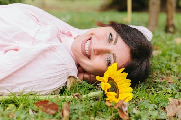 Szczęśliwa kobieta z kwiatem na trawie