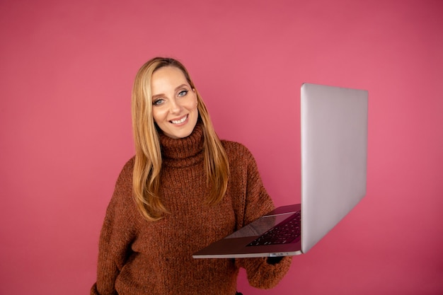 Szczęśliwa kobieta z laptopem na białym tle w różowym studio.