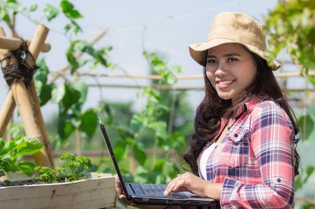 Szczęśliwa kobieta z laptopem w gospodarstwie rolnym