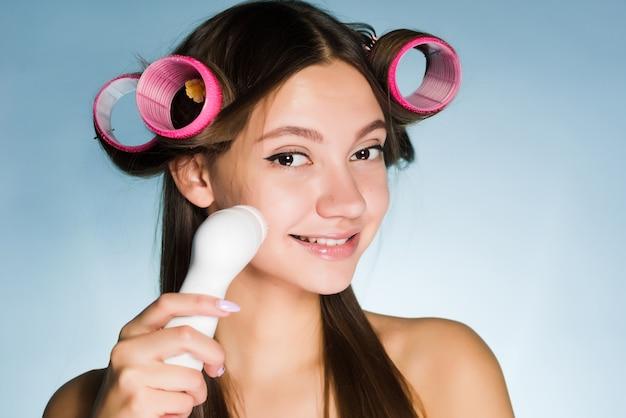 Szczęśliwa kobieta z lokówkami na głowie czyści skórę twarzy szczoteczką do głębokiego czyszczenia