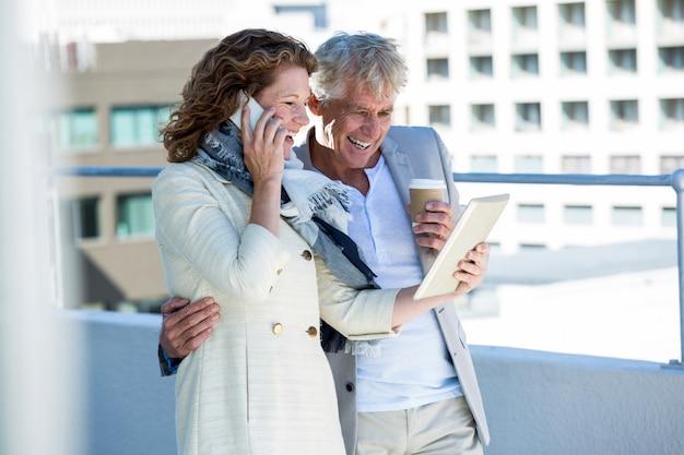 Szczęśliwa kobieta z mężczyzna używa cyfrową pastylkę