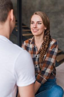 Szczęśliwa kobieta z mężczyzną w miłości siedzi w pomieszczeniu
