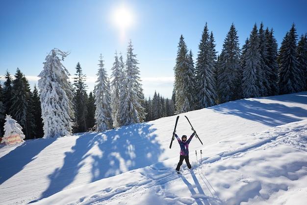 Szczęśliwa kobieta z nart stojących pośrodku zaśnieżonego stoku góry. słoneczny dzień podczas ferii zimowych. ogólna perspektywa.