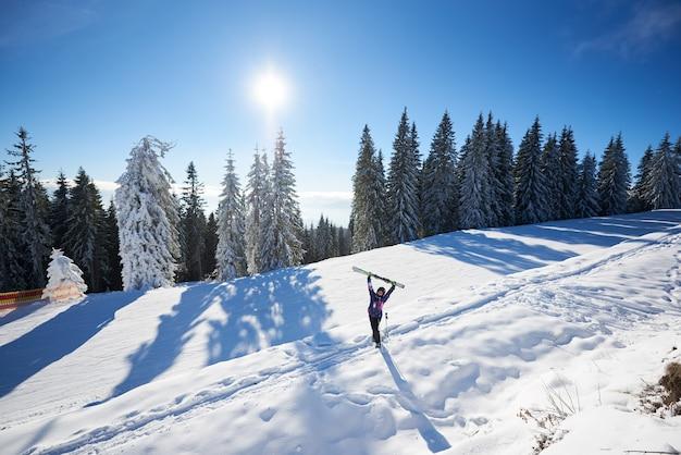Szczęśliwa kobieta z nartami stojąc w środku zaśnieżonego stoku góry. słoneczny dzień podczas ferii zimowych. ogólna perspektywa.