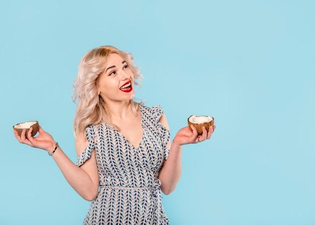 Szczęśliwa kobieta z połówkami kokosa