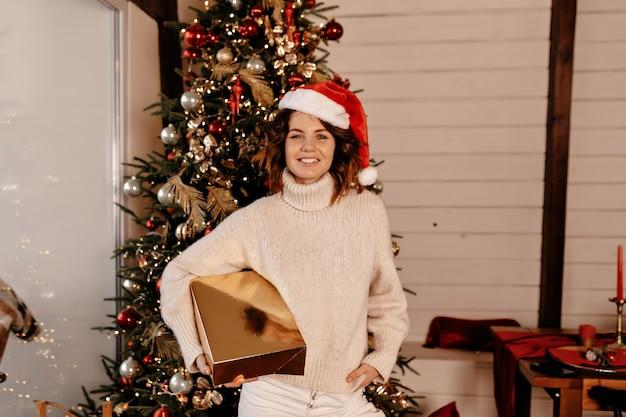 Szczęśliwa kobieta z prezentem bożonarodzeniowym.
