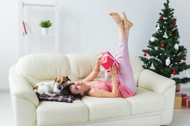 Szczęśliwa kobieta z psem i choinką z prezentami pod nim