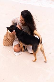 Szczęśliwa kobieta z psem na plaży