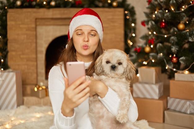 Szczęśliwa kobieta z psem robi selfie w świątecznej dekoracji, kobieta wysyła gest pocałunku do aparatu smartfona, trzymając usta zaokrąglone, ubrana w biały swobodny sweter i czapkę świętego mikołaja.