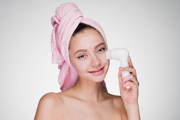 Szczęśliwa kobieta z ręcznikiem na głowie czyści skórę twarzy szczoteczką do głębokiego wirowania
