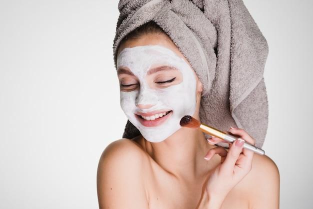 Szczęśliwa kobieta z ręcznikiem na głowie po prysznicu nakłada się na skórę maski na twarz