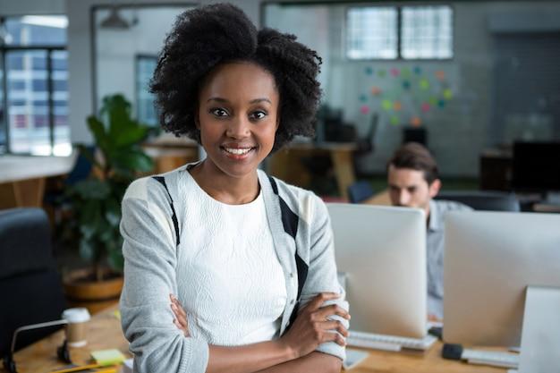 Szczęśliwa kobieta z rękami skrzyżowanymi stojąc w biurze