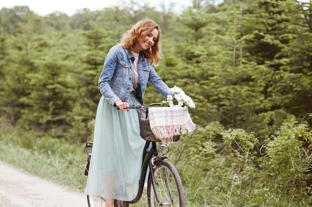 Szczęśliwa kobieta z rowerem w parku