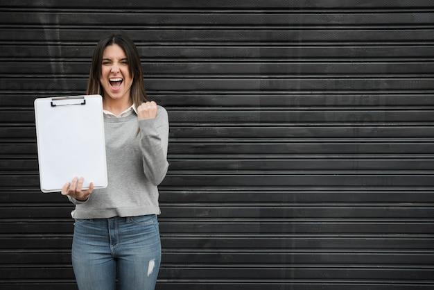 Szczęśliwa kobieta z schowkiem na czarnym profilującym prześcieradle