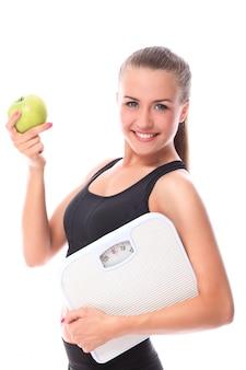 Szczęśliwa kobieta z skala i zielonym jabłkiem