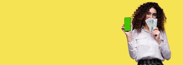Szczęśliwa kobieta z smartphone trzymając gotówkę, szczęśliwa kobieta wygrywająca zakład gotówkowy kasyno online, kaukaski kobieta na żółtym tle