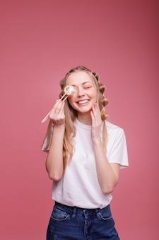 Szczęśliwa kobieta z sushi uśmiecha się na różowej powierzchni