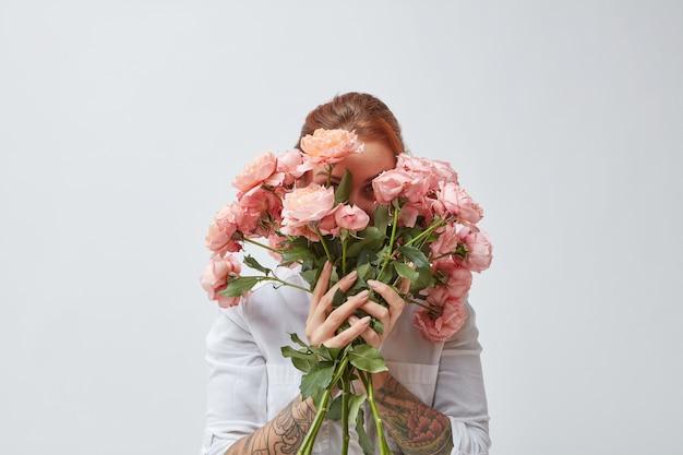 Szczęśliwa kobieta z tatuażem na dłoniach chowa twarz za bukietem pachnących różowych róż. dzień matki