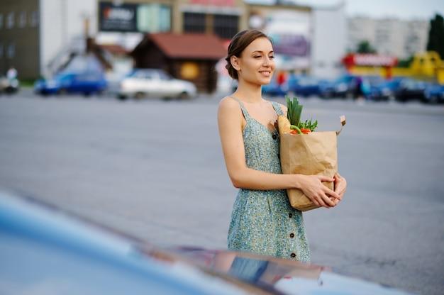Szczęśliwa kobieta z torbą na parkingu samochodowym w supermarkecie