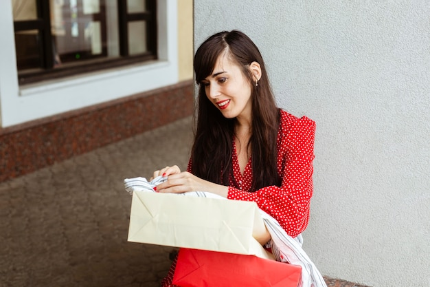 Szczęśliwa kobieta z torba na zakupy i sprzedaż odzieży