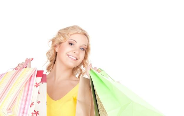 Szczęśliwa kobieta z torbami na zakupy na białej ścianie