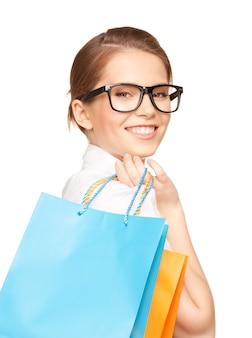 Szczęśliwa kobieta z torbami na zakupy nad białymi