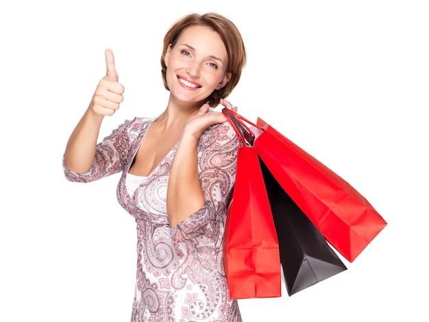 Szczęśliwa kobieta z torby na zakupy po zakupach pokazując kciuki do góry gest