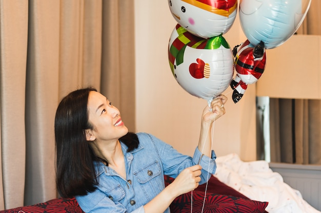 Szczęśliwa kobieta z uśmiechu mienia balonem jako teraźniejszość dla specjalnego dnia w domu.